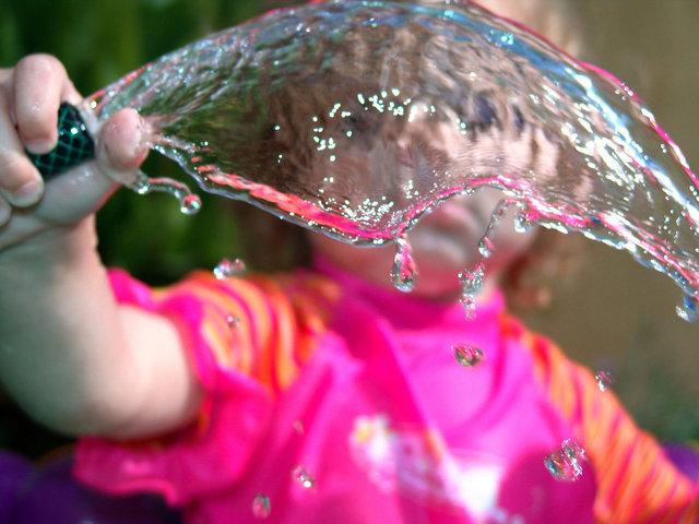 dítě drží hadici s vodou